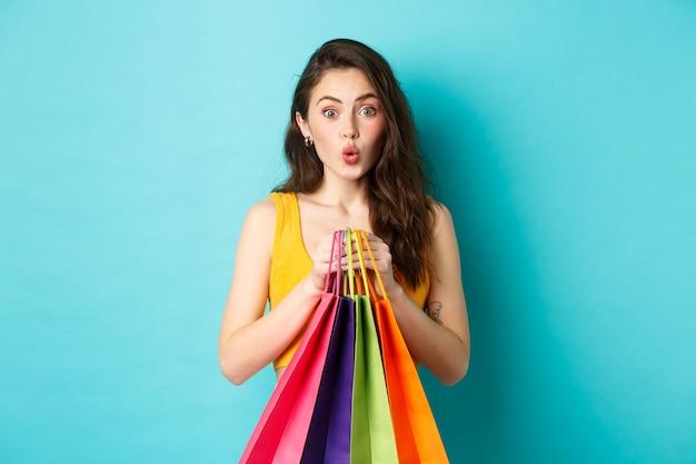 Une jeune femme séduisante a l'air intriguée par l'offre promotionnelle, tenant des sacs à provisions avec des marchandises, debout sur fond bleu. espace de copie