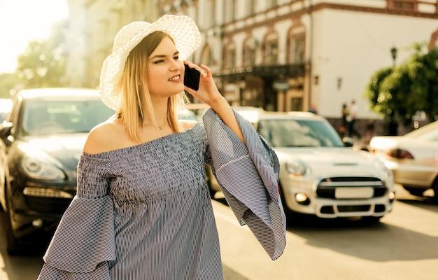 Une jeune femme séduisante appelle un taxi au téléphone sur la chaussée de la ville. concept d'auto-stop
