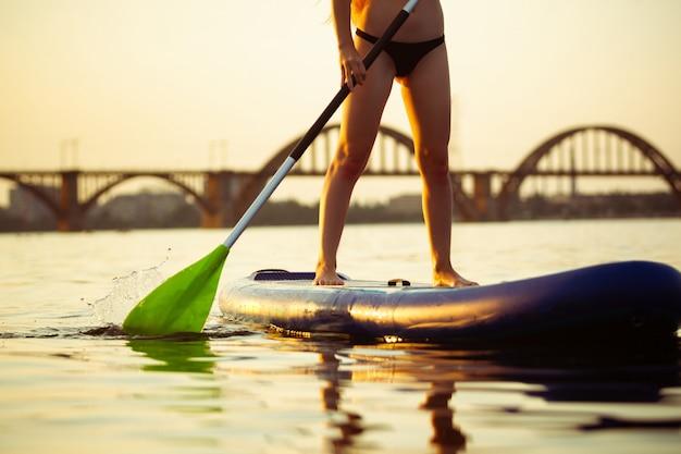 Jeune femme séduisante assise sur le paddle board