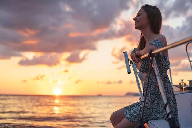 Jeune femme séduisante assise sur le pont du yacht et profitant du coucher du soleil