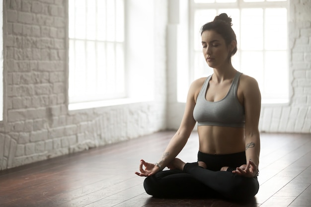 Jeune femme séduisante assise en posture de lotus, studio loft blanc