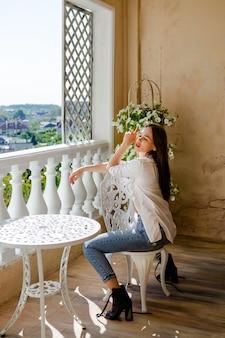 Jeune femme séduisante assise sur la terrasse près de la table