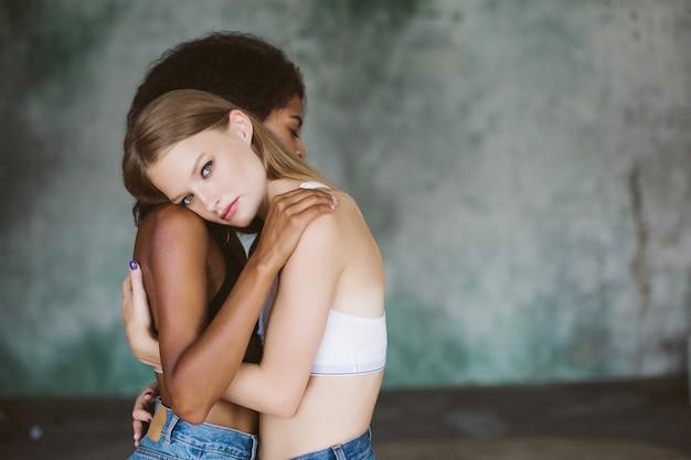 Jeune femme séduisante aux cheveux blonds en haut étreignant petite amie afro-américaine tout en pensant