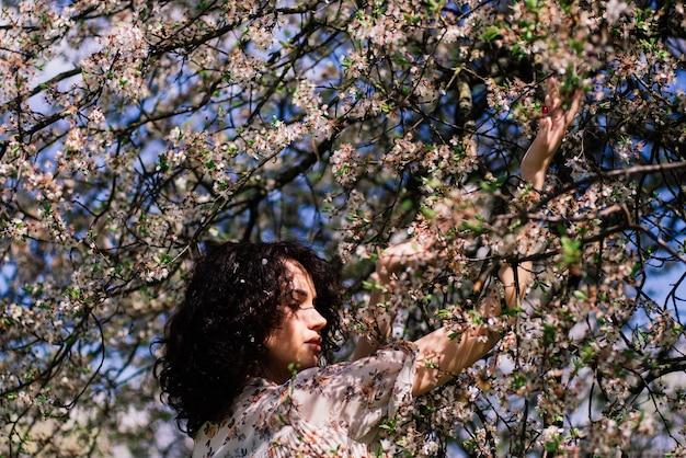 Jeune femme séduisante aux cheveux longs bouclés posant dans un jardin fleuri de printemps, des pommiers