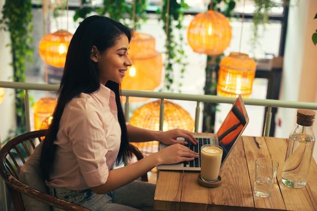 Jeune femme séduisante aux cheveux longs dans un chemisier mettant ses mains sur le clavier d'un ordinateur portable et souriant alors qu'il était assis dans un café