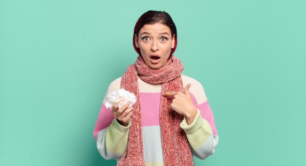 Jeune femme séduisante aux cheveux rouges à la choqué et surpris avec la bouche grande ouverte, pointant vers le concept de grippe auto