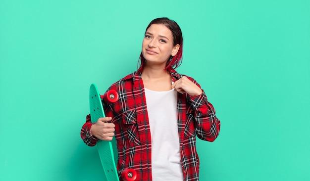 Jeune femme séduisante aux cheveux roux à l'air arrogante, réussie, positive et fière, se montrant elle-même et tenant une planche à roulettes
