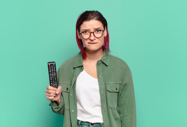 Jeune femme séduisante aux cheveux roux à l'air perplexe et confus, mordant la lèvre avec un geste nerveux, ne connaissant pas la réponse au problème et tenant une télécommande de télévision