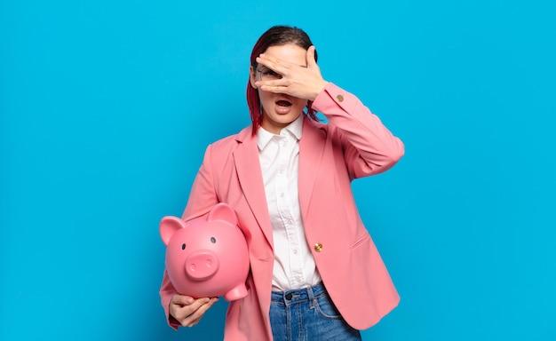 Jeune femme séduisante aux cheveux roux ayant l'air choquée, effrayée ou terrifiée, couvrant le visage avec la main et regardant entre les doigts. concept d'entreprise humoristique.