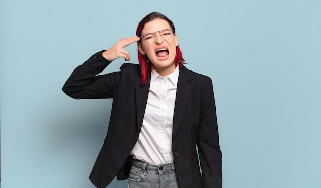 Jeune femme séduisante aux cheveux roux à la malheureuse et stressée, geste de suicide faisant signe des armes à feu avec la main, pointant vers la tête