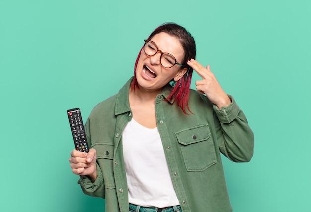 Jeune femme séduisante aux cheveux roux à la malheureuse et stressée, geste de suicide faisant signe de pistolet avec la main, pointant vers la tête et tenant une télécommande de télévision