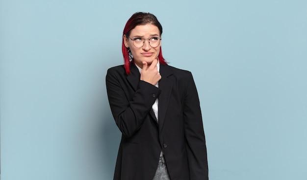 Jeune femme séduisante aux cheveux roux pensant, se sentant dubitative et confuse, avec différentes options, se demandant quelle décision prendre