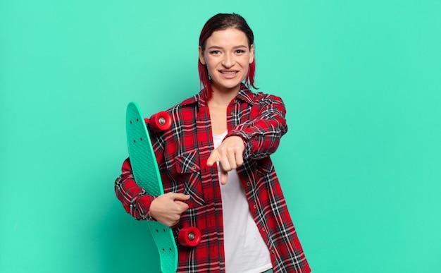Jeune femme séduisante aux cheveux roux pointant vers la caméra avec un satisfait