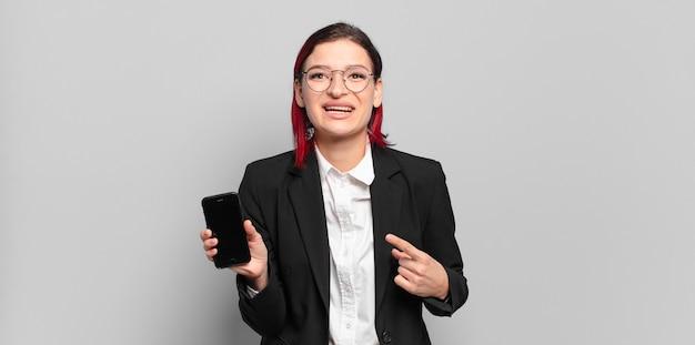 Jeune femme séduisante aux cheveux roux à la recherche excitée et surprise en pointant vers le côté et vers le haut pour copier l'espace. concept d'entreprise