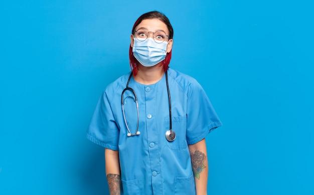 Jeune femme séduisante aux cheveux roux à la recherche heureuse et agréablement surprise, excitée par une expression fascinée et choquée. concept d & # 39; infirmière d & # 39; hôpital