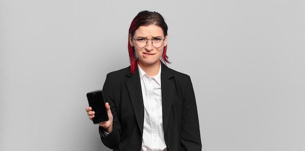 Jeune femme séduisante aux cheveux roux à la recherche perplexe et confuse, mordant la lèvre avec un geste nerveux, ne sachant pas la réponse au problème. concept d'entreprise