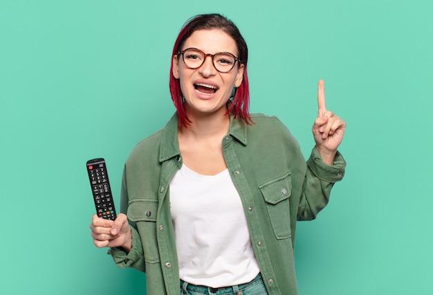 Jeune femme séduisante aux cheveux roux se sentant comme un génie heureux et excité après avoir réalisé une idée