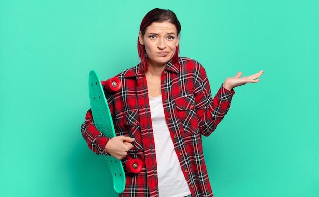 Jeune femme séduisante aux cheveux roux se sentant perplexe et confuse, doutant, pondérant ou choisissant différentes options avec une expression drôle et tenant une planche à roulettes
