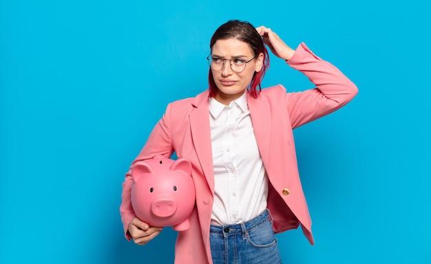 Jeune femme séduisante aux cheveux roux se sentant perplexe et confuse, se gratte la tête et regarde sur le côté. concept d'entreprise humoristique.