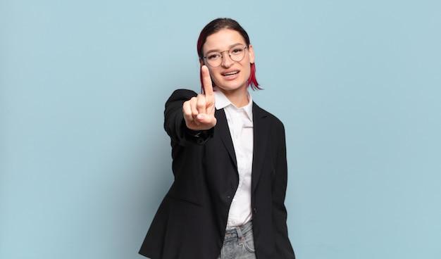 Jeune femme séduisante aux cheveux roux souriant fièrement et en toute confiance faisant le numéro un pose triomphalement, se sentant comme un leader