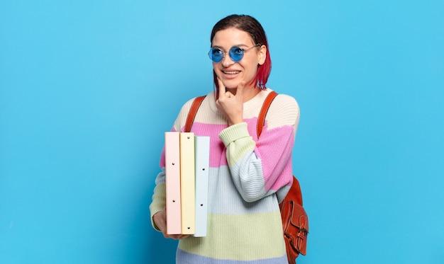 Jeune femme séduisante aux cheveux roux souriant joyeusement et rêvassant ou doutant, regardant sur le côté. concept d'étudiant universitaire