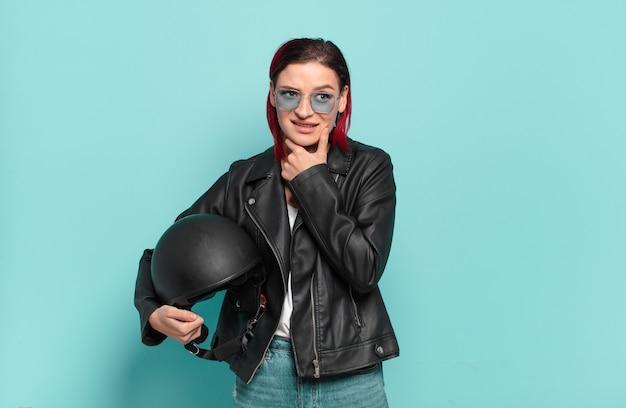 Jeune femme séduisante aux cheveux roux souriant joyeusement et rêvassant ou doutant, regardant sur le côté. concept de motocycliste