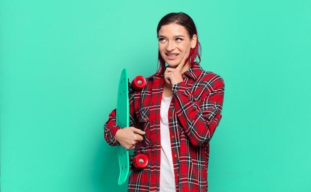 Jeune femme séduisante aux cheveux roux souriant joyeusement et rêvassant ou doutant, regardant sur le côté et tenant une planche à roulettes