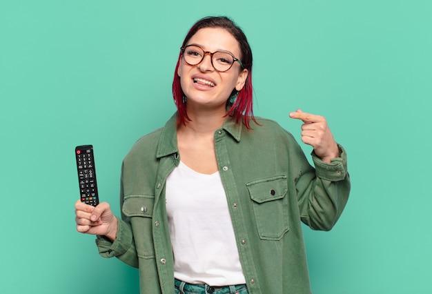 Jeune femme séduisante aux cheveux roux souriant pointant avec confiance vers son propre large sourire, attitude positive, détendue, satisfaite et tenant une télécommande de télévision