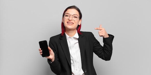 Jeune femme séduisante aux cheveux roux souriante pointant avec confiance vers son propre large sourire, attitude positive, détendue et satisfaite. concept d'entreprise