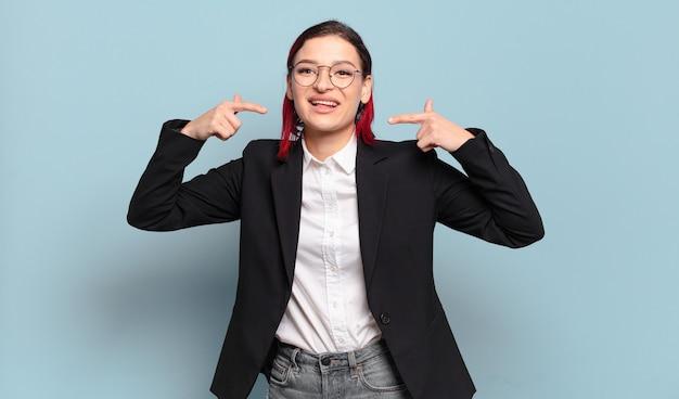 Jeune femme séduisante aux cheveux roux souriante pointant avec confiance vers son propre large sourire, attitude positive, détendue et satisfaite