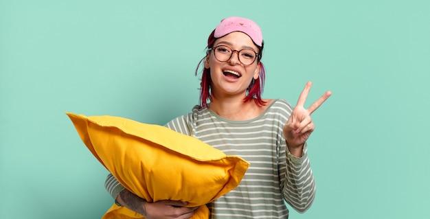 Jeune femme séduisante aux cheveux roux souriante et semblant heureuse, insouciante et positive, gesticulant la victoire ou la paix d'une main et portant un pyjama