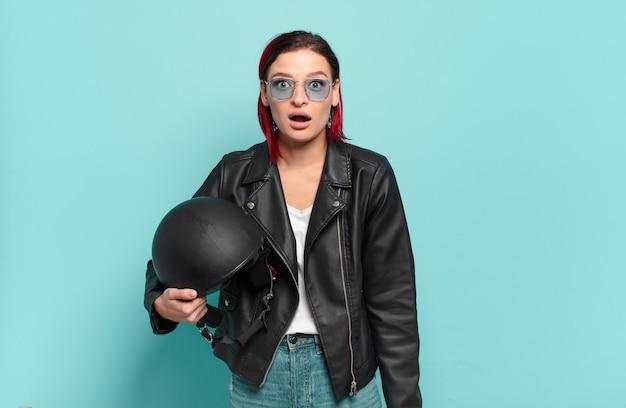 Jeune femme séduisante aux cheveux roux, très choquée ou surprise, regardant la bouche ouverte en disant wow. concept de motard