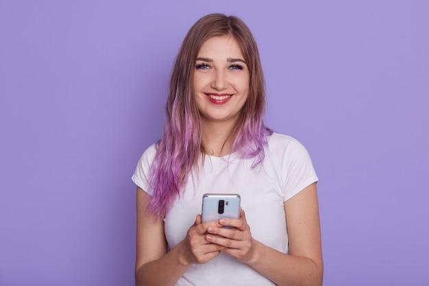 Jeune femme séduisante aux cheveux violets regardant directement la caméra avec une expression faciale heureuse, tenant un téléphone portable, reçoit un message avec de bonnes nouvelles, isolée sur fond lilas.
