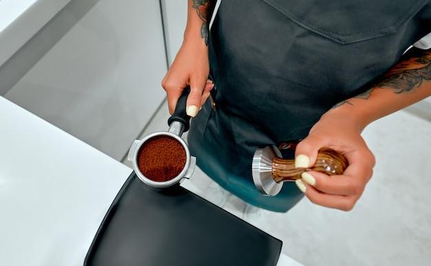 Jeune femme séduisante, barista presse du café moulu à l'aide d'un tamper dans un café.