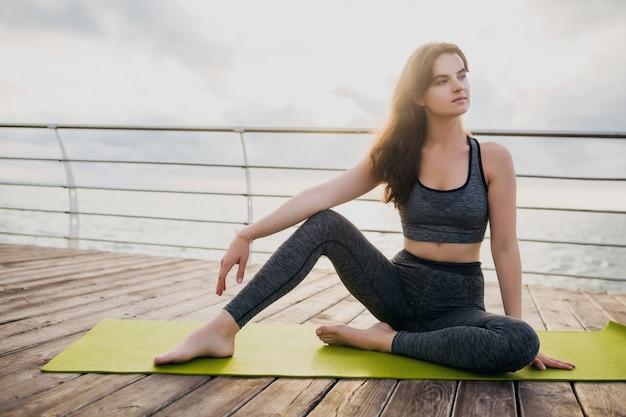 Jeune femme séduisante belle mince se détendre sur un tapis de yoga le matin au lever du soleil en mer, mode de vie sain, sport de remise en forme