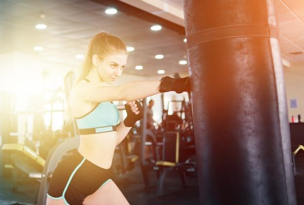 Jeune femme séduisante boxe et formation son coup de poing avec sac de boxe dans la salle de sport