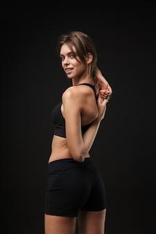 Jeune femme séduisante et confiante en bonne santé portant un soutien-gorge de sport et un short isolé sur fond noir, faisant des exercices d'étirement