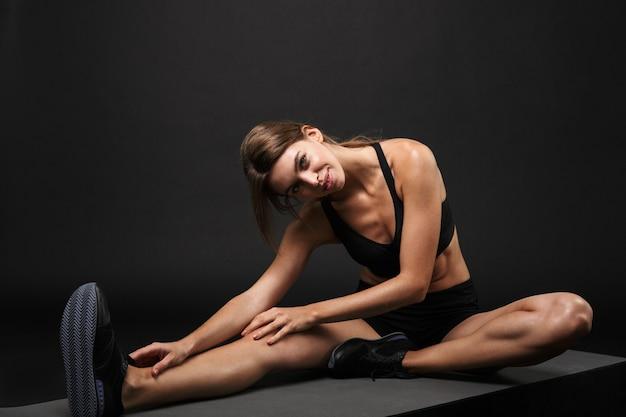 Jeune femme séduisante et confiante en bonne santé portant un soutien-gorge de sport et un short isolé sur fond noir, s'exerçant sur un tapis de fitness, étirement de yoga