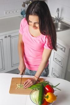 Jeune femme séduisante cuisine salade à l'intérieur à la cuisine