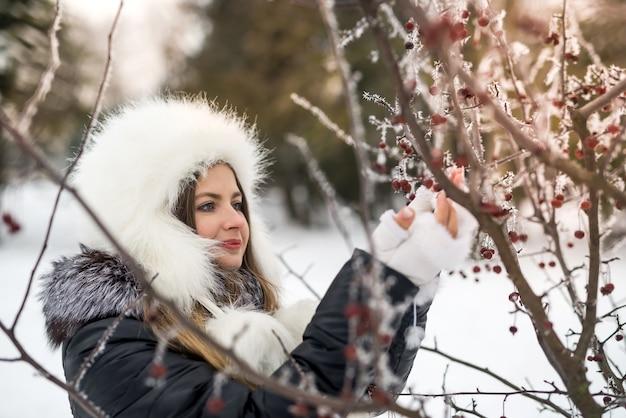 Jeune femme séduisante dans le parc d'hiver avec des branches d'arbres