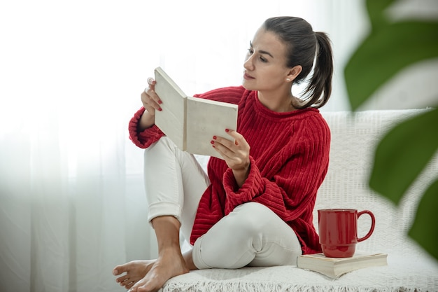 Jeune femme séduisante dans un pull rouge confortable lit un livre assis à la maison sur le canapé avec une tasse de boisson.