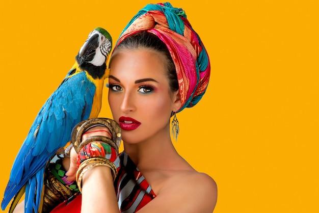 Jeune femme séduisante dans un style africain avec perroquet ara sur sa main sur fond coloré