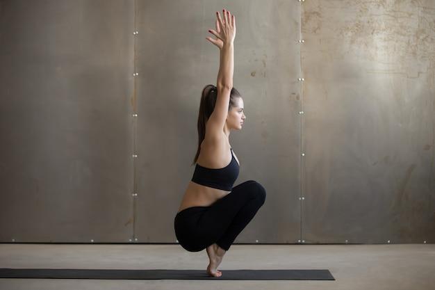 Jeune femme séduisante dans utkatasana pose, studio gris backgroun