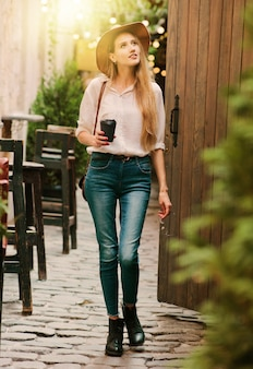 Jeune femme séduisante dans des vêtements de style décontracté marchant le long de la cour de la vieille ville avec une tasse de café sur le pouce
