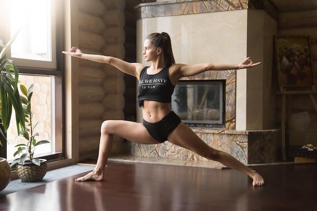Jeune femme séduisante dans warrior two pose, backgr intérieur maison