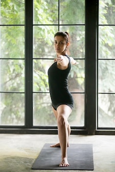 Jeune femme séduisante dans warrior two pose, fond de studio