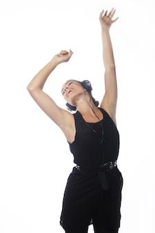 Jeune femme séduisante dansant au son de la musique avec des écouteurs sur blanc