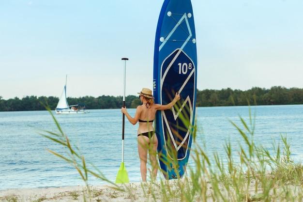 Jeune femme séduisante debout à côté de paddle board