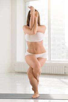 Jeune femme séduisante debout dans la pose de garudasana, couleur blanche