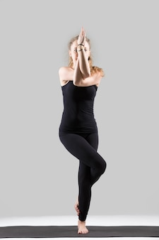 Jeune femme séduisante debout dans la pose de garudasana, studio gris